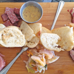 Charcuterie board: Clockwise from top left: dried grapes, landjager, grainy mustard, capicola, pickled fiddlehead ferns, pork rillette, Finger Lakes Kimchee, speck (bread in the middle).