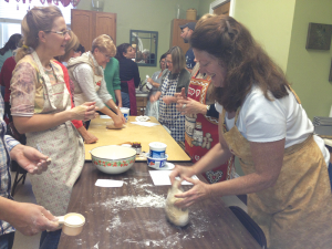 Rev. Ramerman joins a group in baking bread at a Spiritus retreat. Spiritus Christi's pastor Rev. Mary Ramerman (right) is a leader in the church along with Father Jim Callan who together create a diverse and flourishing church community.