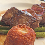 Pan-seared autumn harvest rib steak with charred asparagus spears, potato and blue cheese croquette and raspberry rhubarb glace.