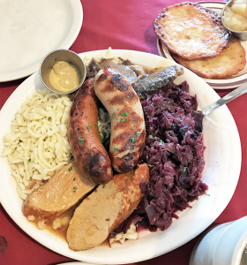 Oma's Teller: The German sampler platter includes sauerbraten, schweinebraten, bratwurst, bauernwurst, red cabbage, spatzle and a side of kartoffelpuffer with chunky apple sauce.