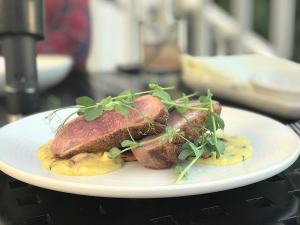 The seared duck breast is served rare with sweet roasted carrots and butternut squash polenta.