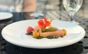 An appetizer of cold-smoked salmon with a vibrant garlic and tarragon puree, blistered cherry tomatoes, capers and sweet pickles.