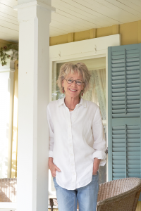 Gwenn Voelcker on the porch of her Mendon home.