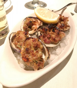 Six tender clams topped with a bread stuffing loaded with bacon, garlic and red pepper, served atop rock salt with a wedge of lemon.