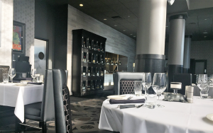 The restaurant has crisp, elegant decor, an open kitchen and large displays of wine.