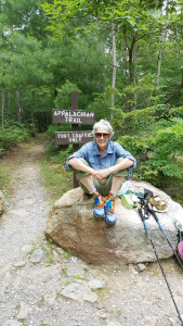 Sandy Wallace rests at a trail entrance.