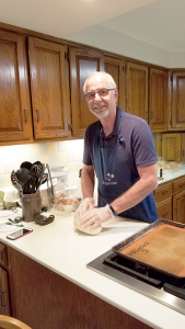 Hands on: Chet Fery in his kitchen in Brockport. He estimates he has baked nearly 100,000 loafs of bread to date — and given them away. Photo by Christine Green.