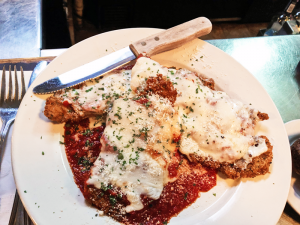 The veal parmesan entree features three loins covered in marinara sauce and melted mozzarella.