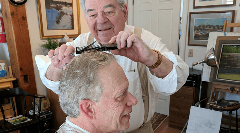 Barber Henry Besanceney at his barber shop in Honeoye Falls with Gary Albright, a client. The shop is filled with antiques, books on wine, paintings and his original art — all that with jazz playing in the background.