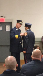 John Welker pins a badge on his son D.J. at the New York State Fire Academy graduation.