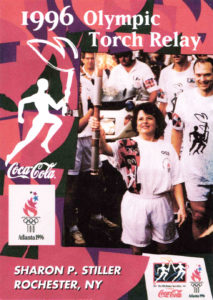 This poster features Sharon Stiller carrying the Olympic torch when it came through Rochester in 1996.