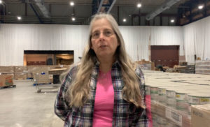 Laura Reitter is a Foodlink volunteer, working to put food boxes together on the floor of the warehouse facility in Kodak Park in Rochester.