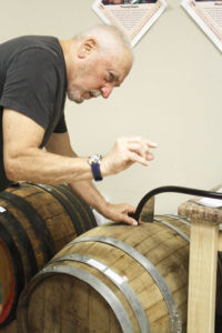 Tom Raco of Webster examining a new batch of wine produced by Wineworx. Raco and his friend Tony Toscano of Rochester created Wineworx in 2013.