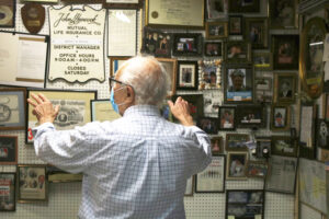 "A story behind every artifact. Mario Arena shows his ""John Hancock"" wall, where he's placed items from his successful 30-year career as an insurance man and agency manager. Point to an item, and you'll hear the whole story about it."