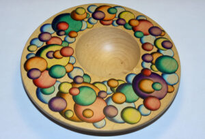 """The Universe of Color"" — Each painted circle has a burned ""border"" around it. Made of maple, acrylic airbrush paint, pyrography. Inspired by a painting by Rochester artist Fritz Trautmann."