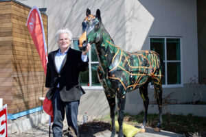 "Howie Jacobson, who ""energized"" the idea of Horses on Parade in Rochester in 2001, stands with ""Journey"" at the Mid-Town Athletic Club. Artist Judith Olson Gregory created the design. Jacobson was chief marketing officer of the new High Falls Brewery, which birthed the project eventually leading to donations of $1.4 million to 114 charities."
