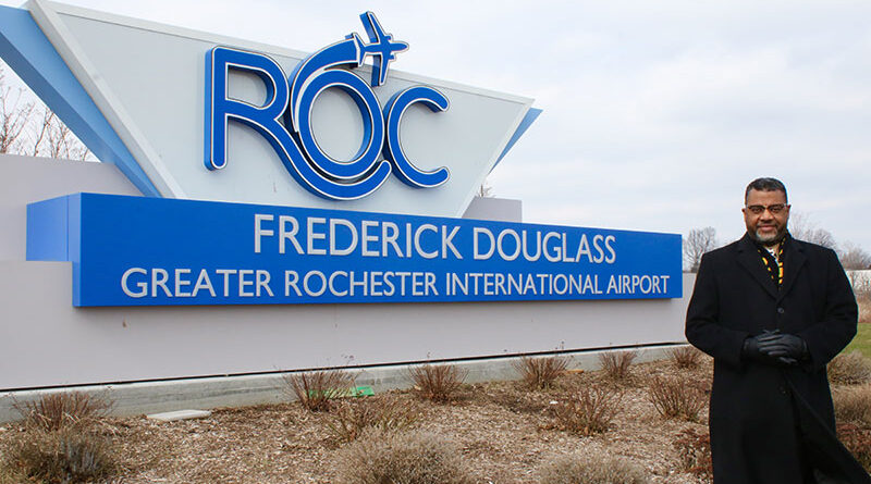 Rev. Julius Jackson Jr. and a sign of the renamed Rochester airport, now known as Frederick Douglass — Greater Rochester International Airport.