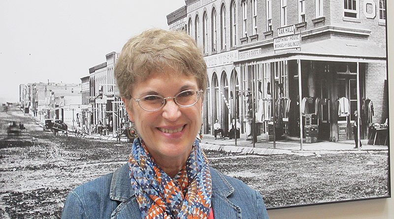 """Jeanne Gehret, a Fairport resident, stands in front of a historical photograph of Leavenworth, Kan., at the City Hall there where she did research for her latest book, """"The Truth About Daniel."""""""