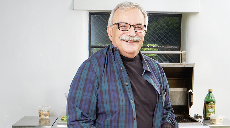 Bill Valente photographed Sept. 6 at his Irondequoit home doing what he enjoys the most — cooking. From the grill that day: heirloom tomatoes and green onions served with freshly grated parmesan cheese, garden fresh basil and grilled crusty Italian bread. Photo by Charles Wainwright