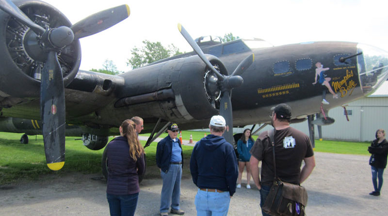 Volunteers explain war era planes at the National Warplane Museum in Geneseo. The Memphis Belle, a B-17 bomber used in the World War II, is in the background. The museum 12 war planes.
