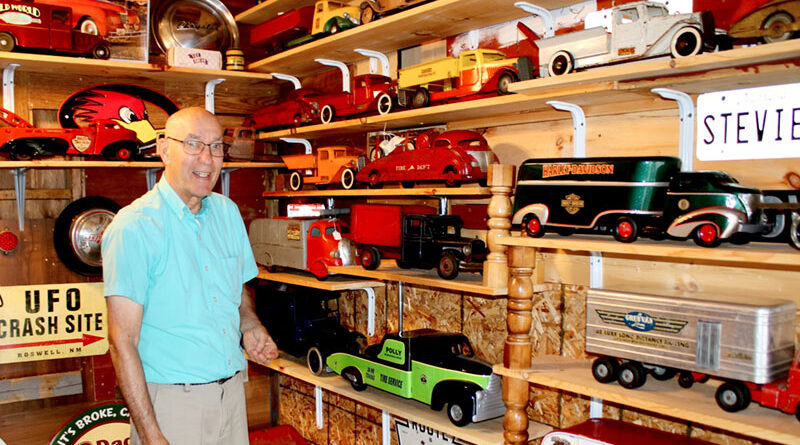 Bill Bangert of Newark stands in his garage next to a portion of his pressed-steel toy car models big enough to be sat on by young children. These car models disappeared in the late 1950s.